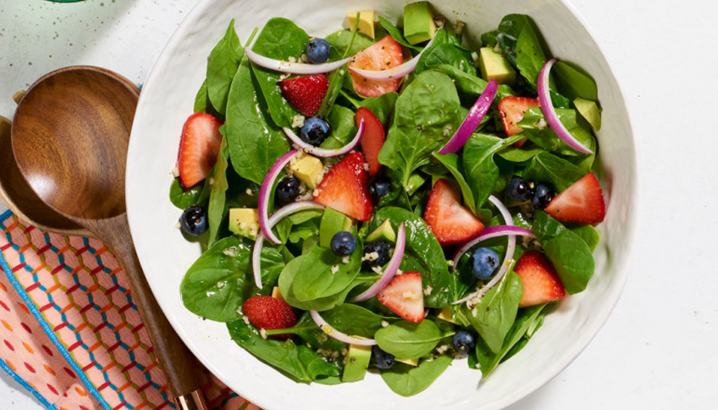 white salad bowl with spinach strawberry blueberries red onions