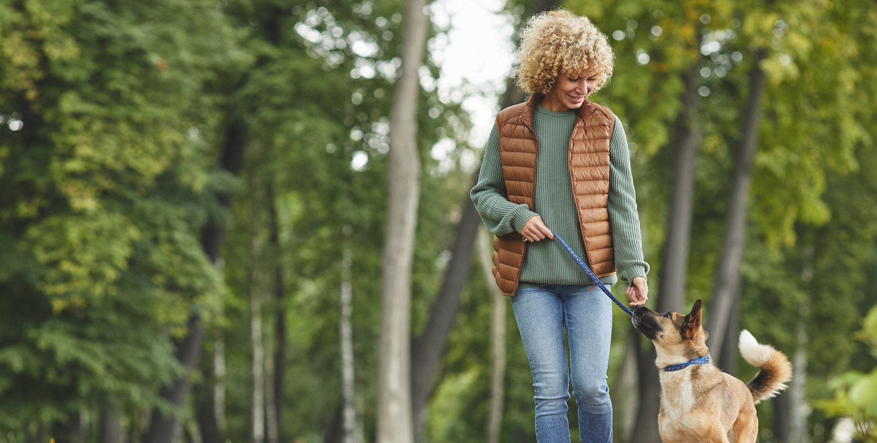 Woman in vest and sweater walking dog