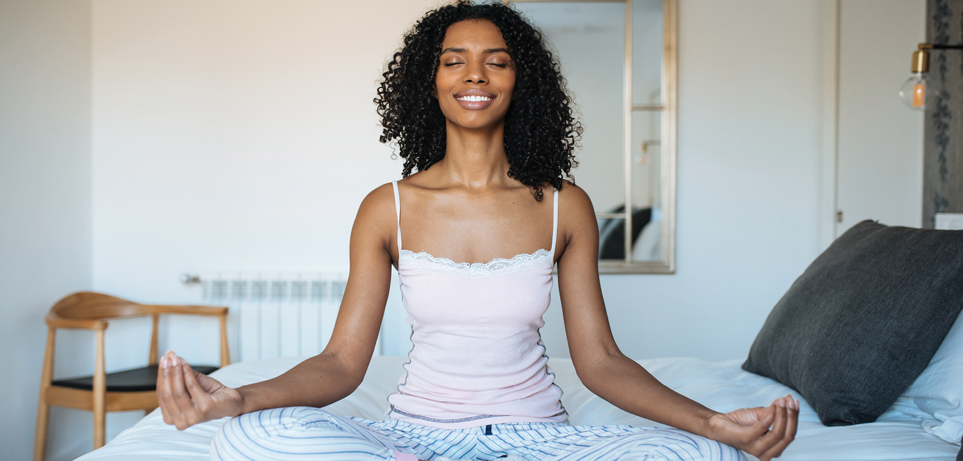 Young woman doing mindful meditation sitting on bed