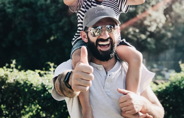 Happy father wearing sunglasses and baseball cap with son on shoulders