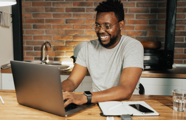 smiling man wearing glasses in kitchen at laptop computer
