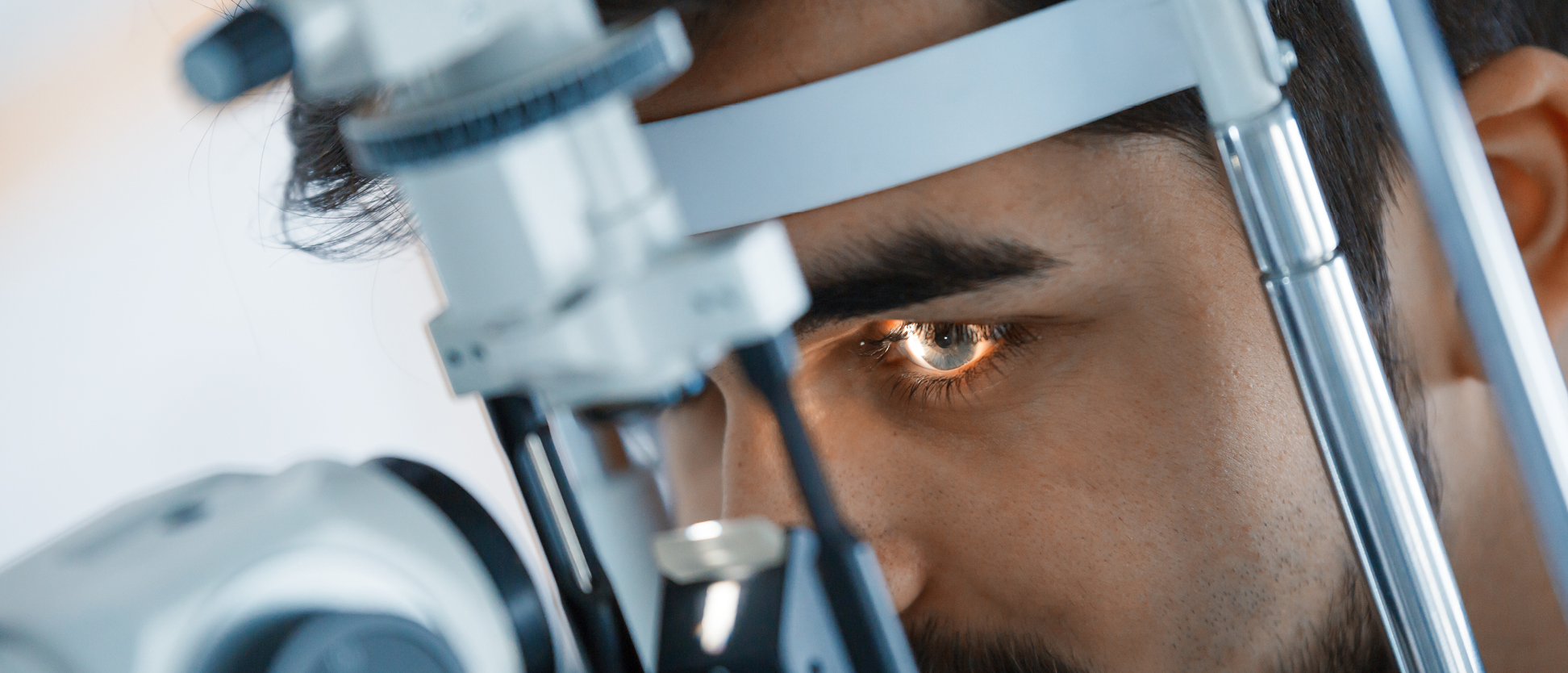 man looking into optometrist eye exam device