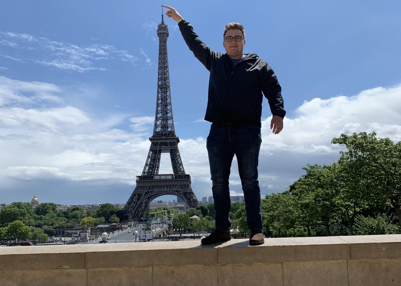 man standing next to the eiffel tower