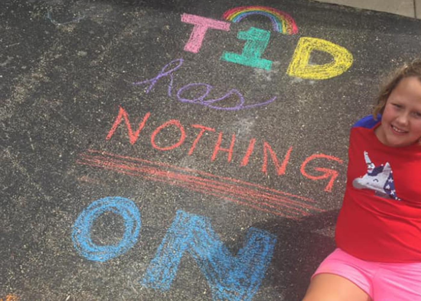 Girl in red shirt on asphalt with colored chalk writing