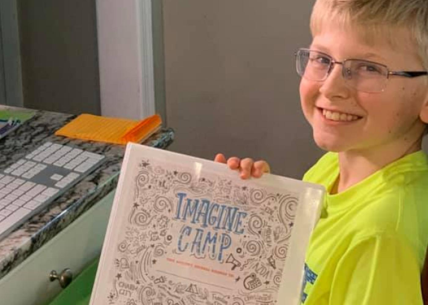 Blond boy with glasses in yellow shirt holding imagine camp piece of paper