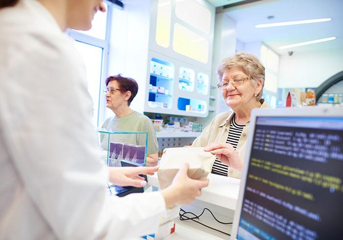 pharmacist-handing-medications-to-senior-woman-customer