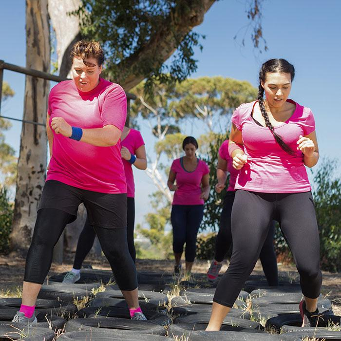 women-pink-shirts-exercise-obstacle-course-tires