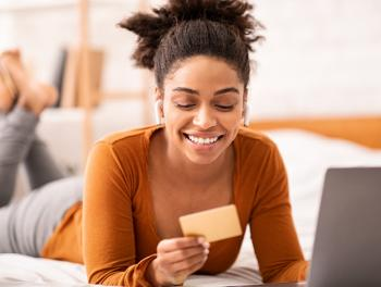 young woman looking at laptop computer with credit card