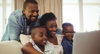 African American mother, father, son, and daughter in front of laptop computer